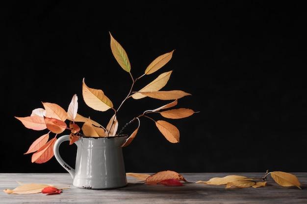 De herfstbladeren in kruik op houten lijst aangaande donkere achtergrond