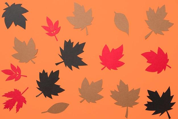 De herfstbladeren van het document op oranje achtergrond