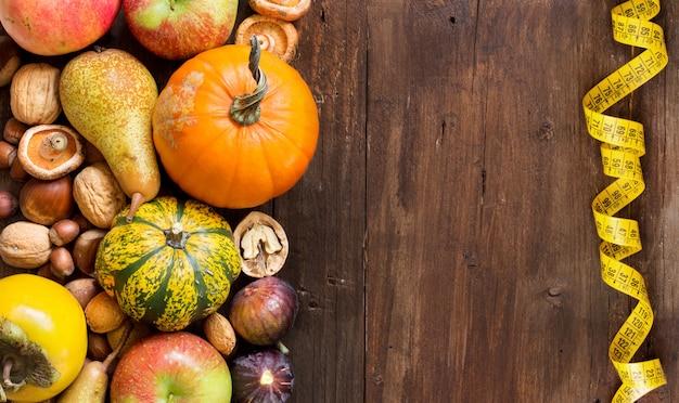 De herfstfruit, groente en muchrooms met het meten van band op de houten mening van de lijstbovenkant met exemplaarruimte