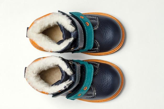 De herfstlaarzen van schattige kinderen isoleren op een witte achtergrond. bovenaanzicht