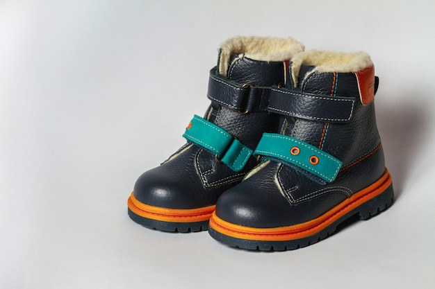 De herfstlaarzen van schattige kinderen isoleren op een witte achtergrond