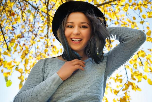 De herfstportret van een jong gelukkig vrouwenmeisje met de herfst sunny park