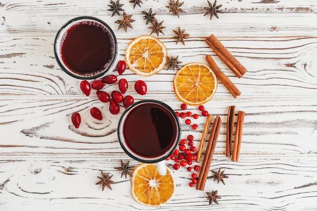 De herfstsamenstelling met hete overwogen wijn en kruiden op houten achtergrond