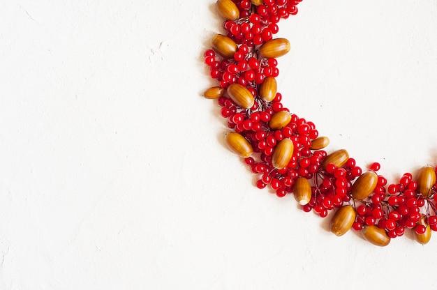 De herfstsamenstelling met rode bes en eikels. krans gemaakt van viburnumbessen.