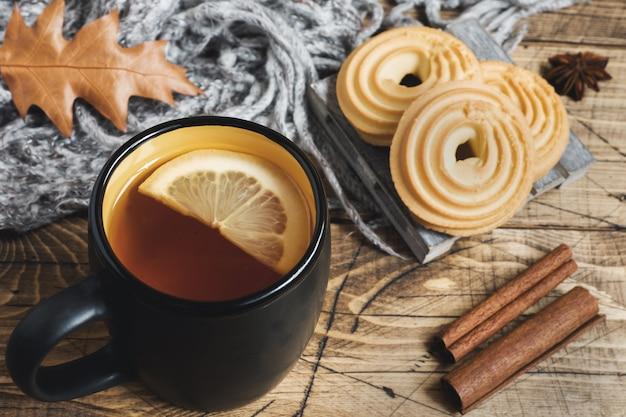De herfststilleven met kop thee, koekjes, sweater en bladeren op houten lijst.