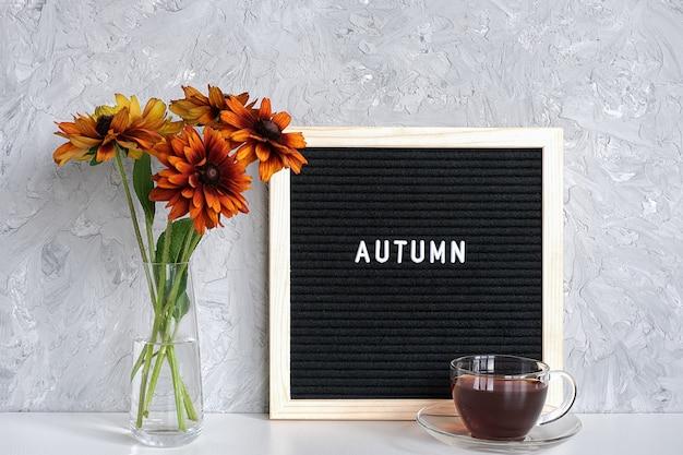 De herfsttekst op zwart brievenraad, boeket van oranje bloemen in vaas en kop thee op lijst tegen grijze steenmuur.