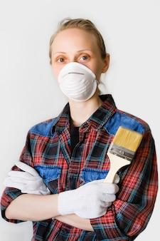 De hersteller, de timmerman, de loonarbeider, de vrouw of het meisje in beschermende handschoenen en masker houden een nieuw schoon penseel, blikken in cel. het concept van thuis en professionele reparatie, bouw.