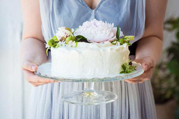 De het huwelijkscake van de vrouwenholding verfraait met bloemen op een glastribune. viering concept. trendy laagjescake