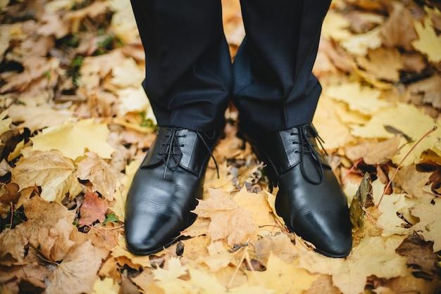 De het huwelijksschoenen van de close-upbruidegom ter plaatse met gouden doorbladert in de herfst