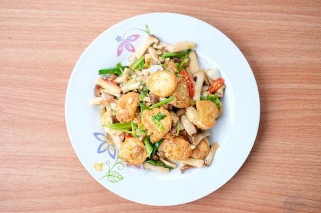 De hete geroerbakte tofu en het varkensvlees en de paddestoel met zwarte bonensaus dienen op witte schotel die op bruine lijst wordt geplaatst - eigengemaakt voedselconcept.