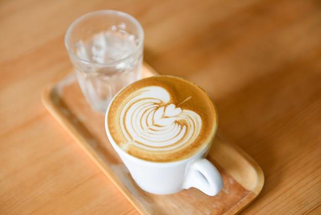 De hete koffie van de cappuccino latte kunst op houten lijst
