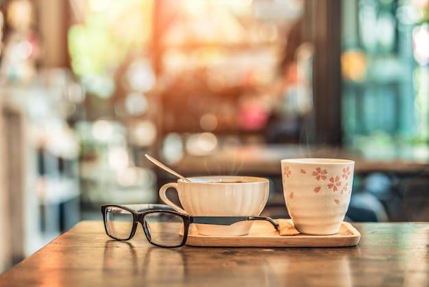 De hete kop van het koffieglas met glazen op houten lijst in koffiewinkel. vintage toon