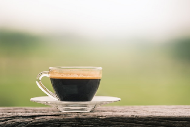 De hete kop van het koffieglas op houten lijst in koffiewinkel met groene natuurlijke achtergrond.