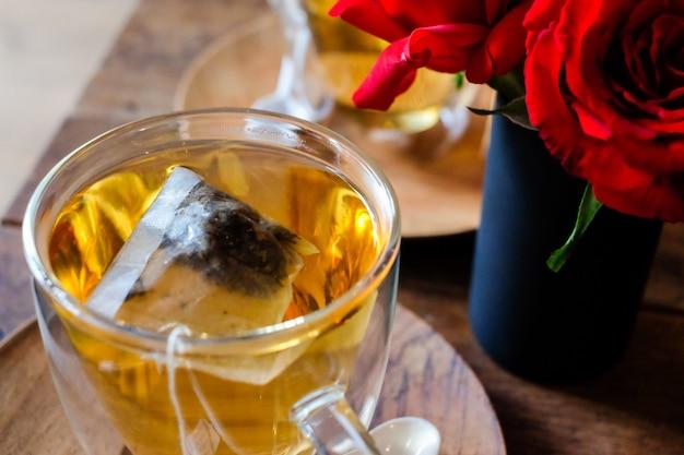 De hete lavendelthee in glas dient met een houten lepel en schotel