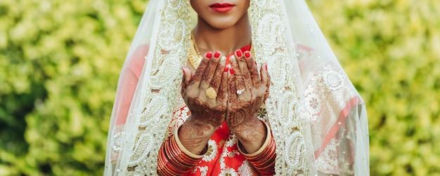 De hindoese bruid in witte sluier heft haar handen op