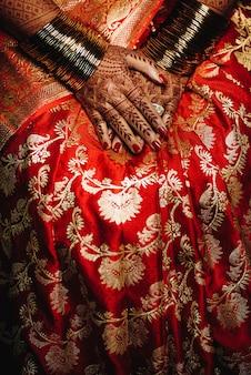 De hindoese bruid toont haar trouwringen op de handen met hennatatt