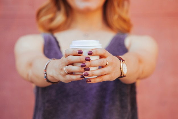 De hipstervrouw die een kop houden van haalt koffie op de straat weg