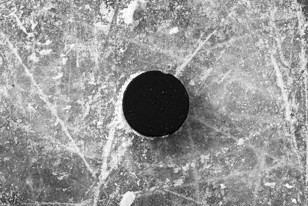 De hockeypuck ligt op het sneeuwclose-up