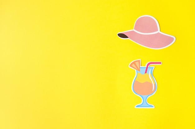 De hoed en de cocktail van fotocabine steunen op gele achtergrond