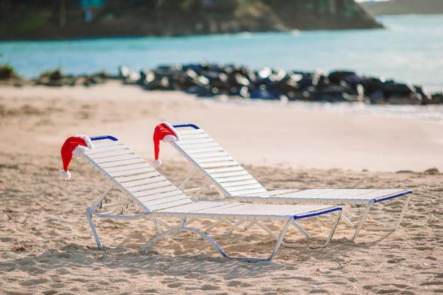 De hoed van close-upsanta op stoel op tropisch wit strand