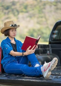 De hoed van de vrouwenslijtage en het lezen van het boek op pick-up