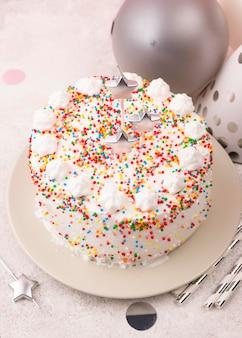 De hoge cake van de hoekverjaardag met kaarsen