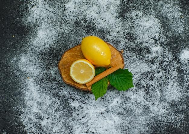 De hoge citroenen van de hoekmening met bladeren en droge kaneel op houten plak en donker. horizontaal