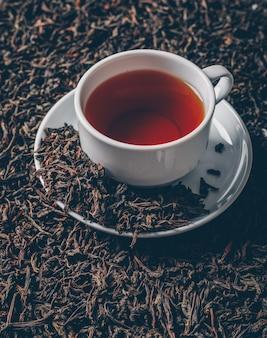 De hoge hoek bekijkt een kop thee op de achtergrond van theekruiden. horizontaal