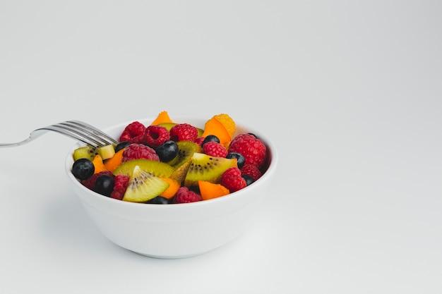 De hoge hoekmening van de close-up van kom vruchten met vork