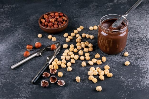 De hoge hoekmening verspreidde schoongemaakte hazelnoten in bruine kom met uitgespreide cacao en notekraker op donkere steenlijst. horizontaal