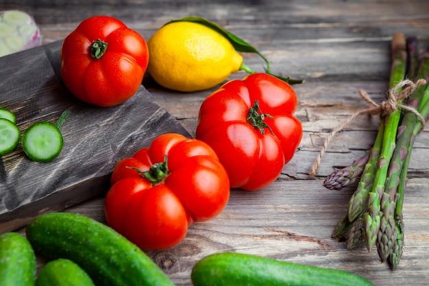 De hoge tomaten van de hoekmening in scherpe raad met gesneden komkommer, knoflook, asperge, citroen op donkere houten achtergrond. horizontaal