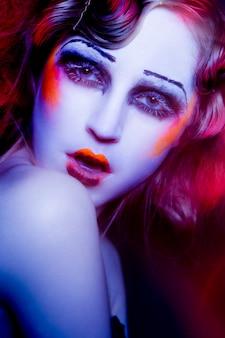 De hoge vrouw van de mannequin in kleurrijke verstralers die in studio stellen