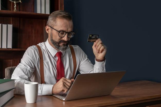 De hogere creditcard die van de bedrijfsmensenholding laptop met behulp van die online in lezingsruimte winkelen