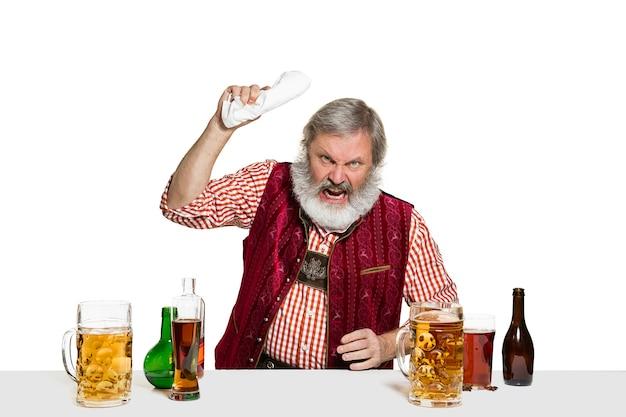 De hogere deskundige mannelijke barman met bier bij geïsoleerd op witte muur.