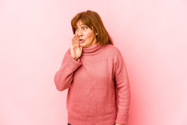 De hogere geïsoleerde kaukasische vrouw zegt een geheim heet remmend nieuws en kijkt opzij