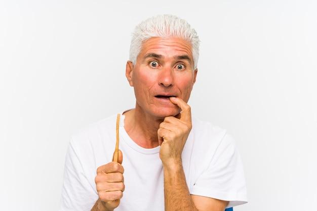 De hogere kaukasische mens die een tandenborstel geïsoleerd houden ontspande het denken over iets bekijkend een exemplaarruimte.
