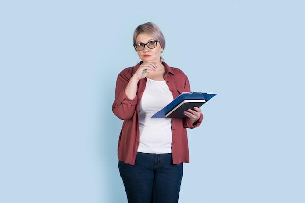 De hogere kaukasische onderneemster stelt op een blauwe studiomuur die enkele omslagen houdt en een bril draagt die naar de camera kijkt