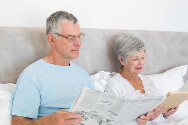 De hogere krant van de mensenholding met het boek van de vrouwenlezing thuis in bed