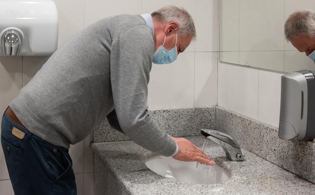 De hogere mens die van hem wast dient een openbaar toilet in