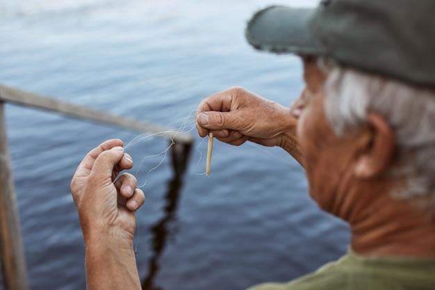 De hogere mens met grijs haar die honkbal glb en de groene hengel van het t-shirtaas dragen, bejaarde mannelijke het besteden tijd dichtbij rivier of meer, die rust in openlucht hebben.