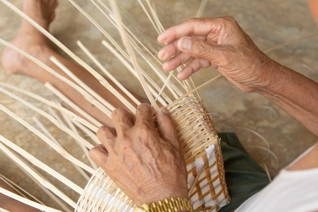 De hogere mens overhandigt handmatig wevend bamboe.
