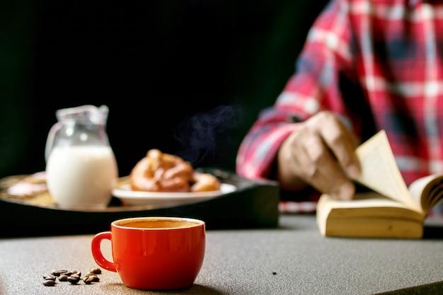 De hogere mensen dragen plaidoverhemd een boek tijdens zijn ontbijt met espresso in rode koffiekop en melk te lezen