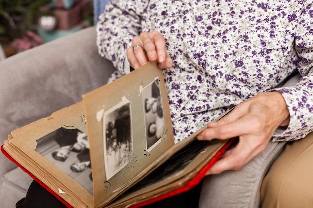 De hogere vrouw die van de close-up fotoalbum onderzoekt