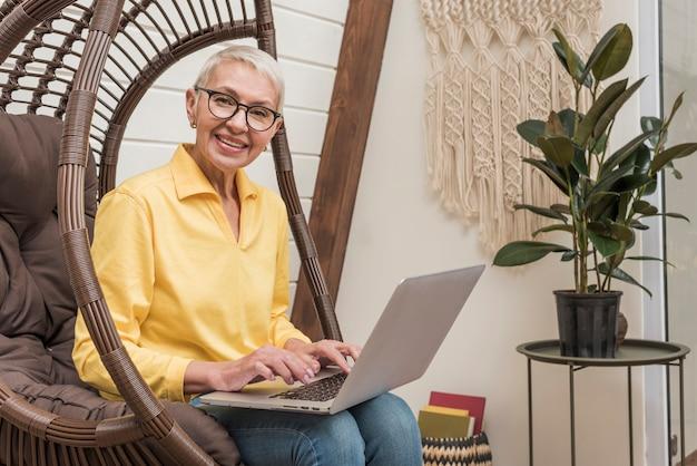 De hogere vrouw die van smiley aan haar laptop werkt