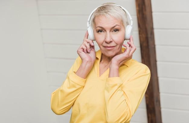 De hogere vrouw die van smiley aan muziek hoewel hoofdtelefoons luistert