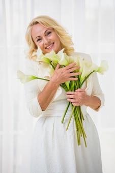 De hogere vrouw die van smiley een boeket van bloemen houdt
