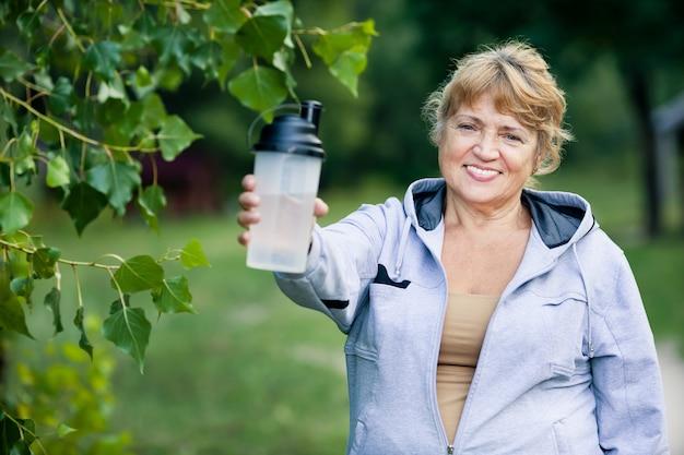 De hogere vrouw houdt een fles water in het park dat sporten doet.
