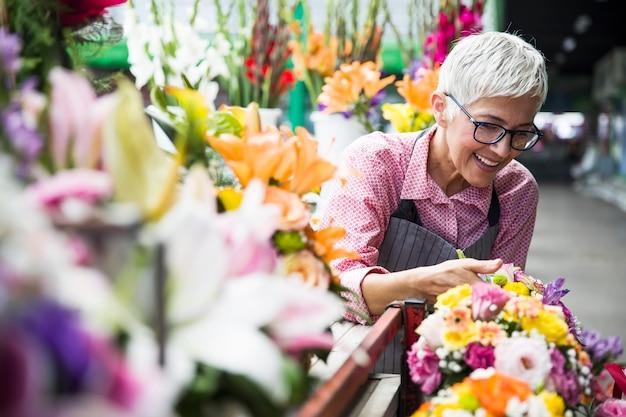 De hogere vrouw schikt bloemen op lokale bloemmarkt