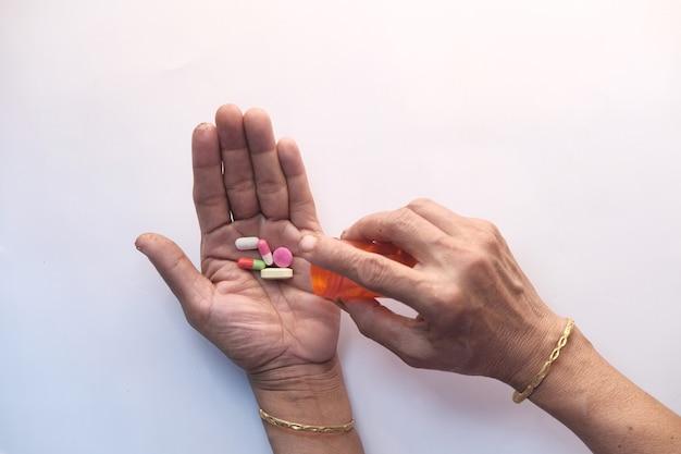 De hogere vrouwenhand die geneeskunde nemen, sluit omhoog.