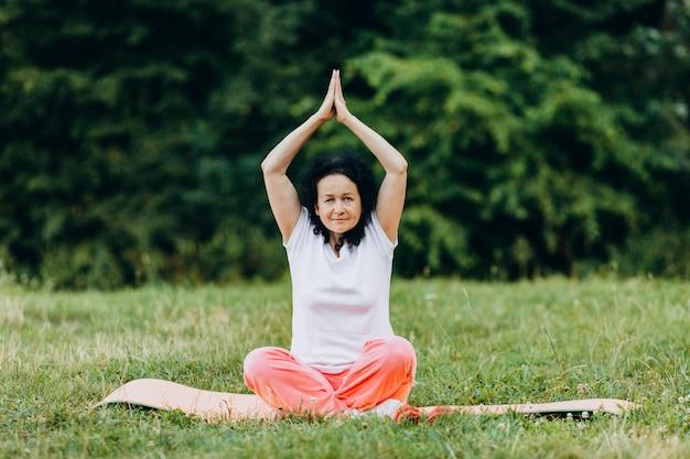 De hogere vrouwenzitting in yoga stelt op yogamat met omhoog handen.